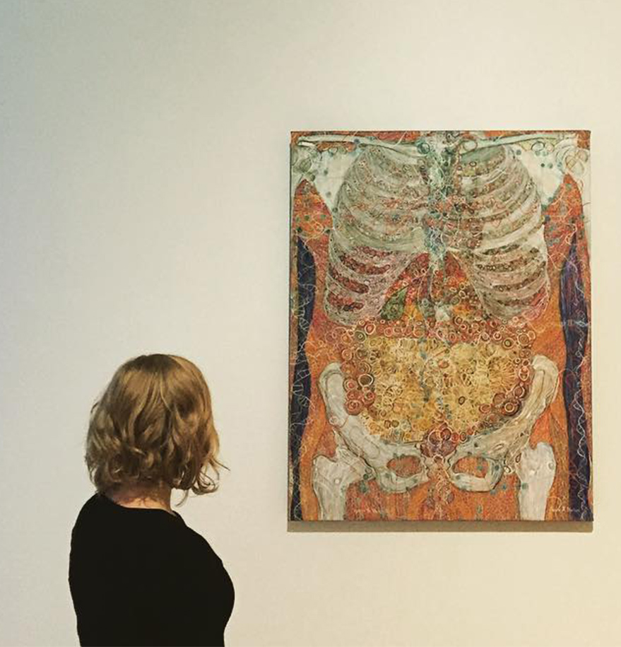Photograph shows a blonde woman in a black sweater, seen mostly from behind, turned towards an anatomical painting of a human torso on a museum wall.